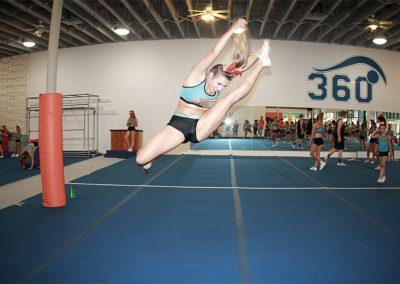 female-cheerleader-doing-mid-air-splits-during-practice-Hurdler