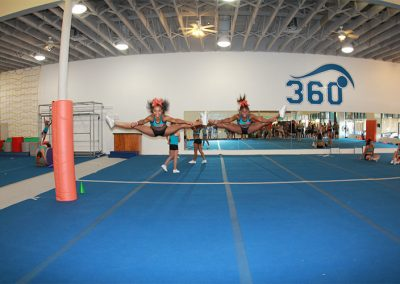 two-female-cheerleaders-doing-toe-touch-cheer-stunt-during-practice-tsunami-3
